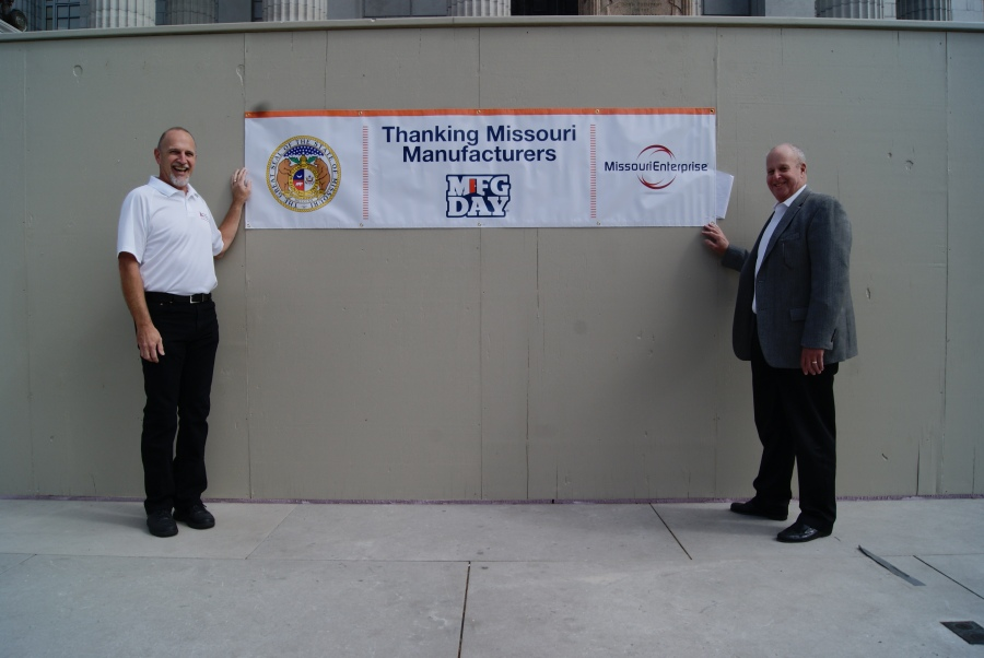 Associated Industries of Missouri President/CEO Ray McCarty (left) and Missouri Enterprise Chief Operating Officer Harold Zinn (right) stand with the banner celebrating National Manufacturing Day, October 2nd, at the State Capitol in Jefferson City.