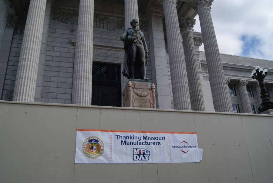 A banner celebrating National Manufacturing Day, October 2, is posted on the temporary wall in front of the south steps of the State Capitol in Jefferson City. The sign was sponsored by Associated Industries of Missouri and Missouri Enterprise.